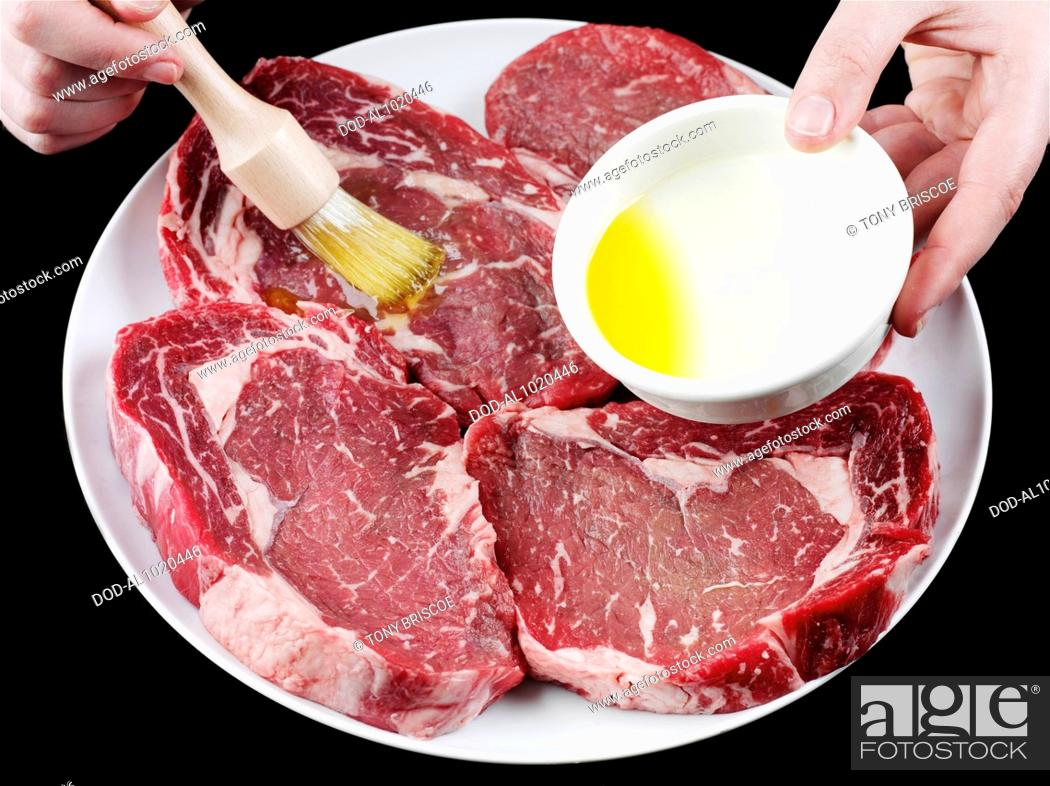 Imagen: Brushing beef steaks with olive oil.