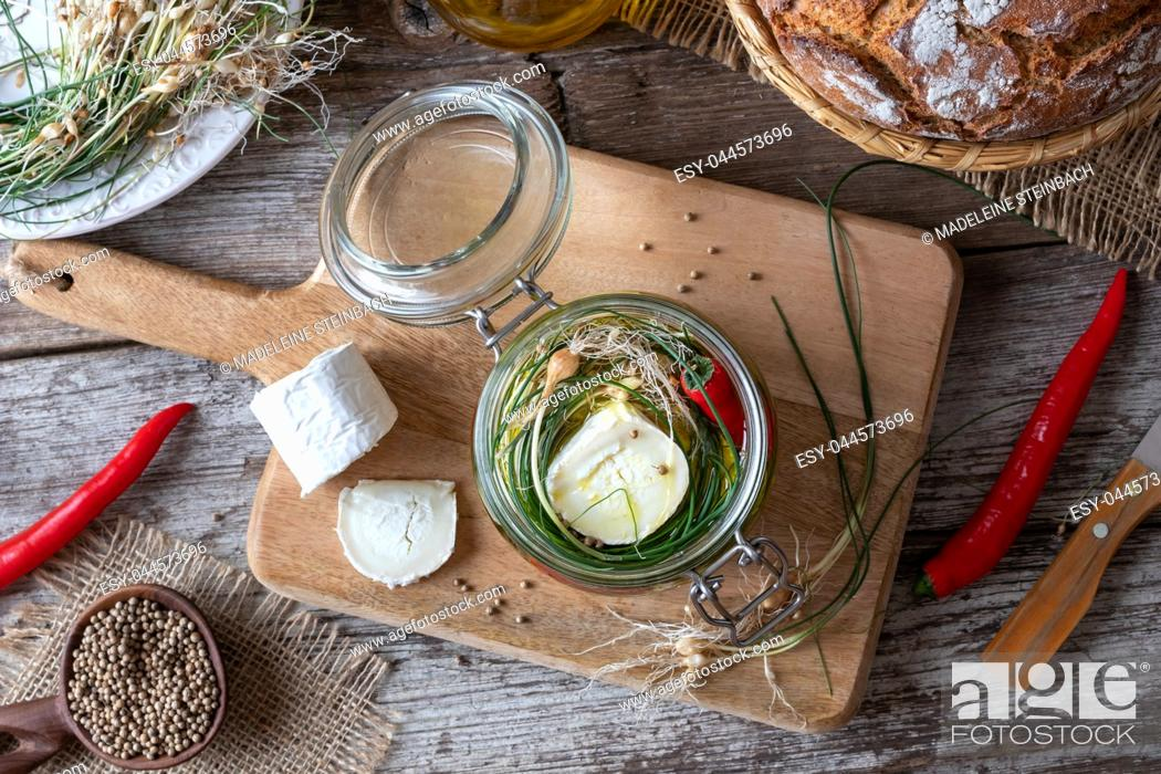 Stock Photo: Marinating goat cheese in oil with wild crow garlic, hot peppers and coriander seeds.