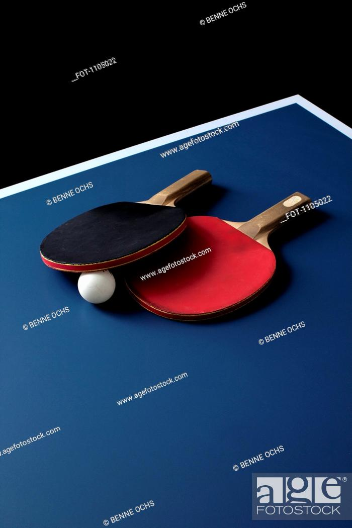 Stock Photo: Table tennis bats and a ball on a table.