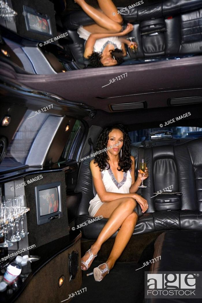 Stock Photo: Young woman with drink in limousine, portrait.
