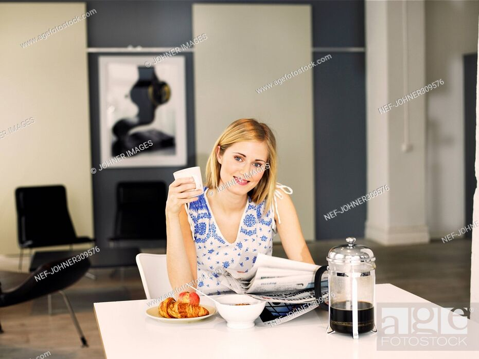 Stock Photo: A woman reading the paper during breakfast.