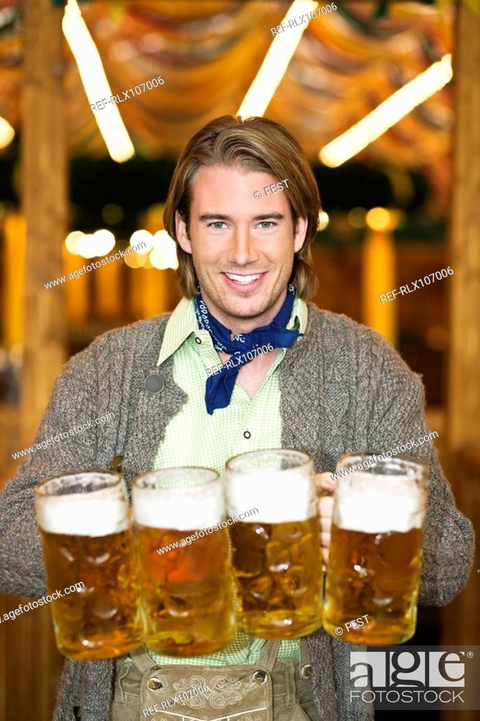 Stock Photo: Waiter holding 4 Mass beer jugs at Oktoberfest, Munich, Germany.