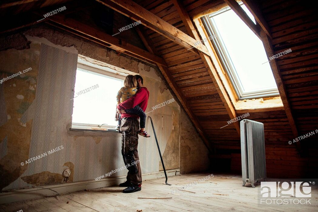 Stock Photo: Full length of father and daughter looking through window in attic under construction.