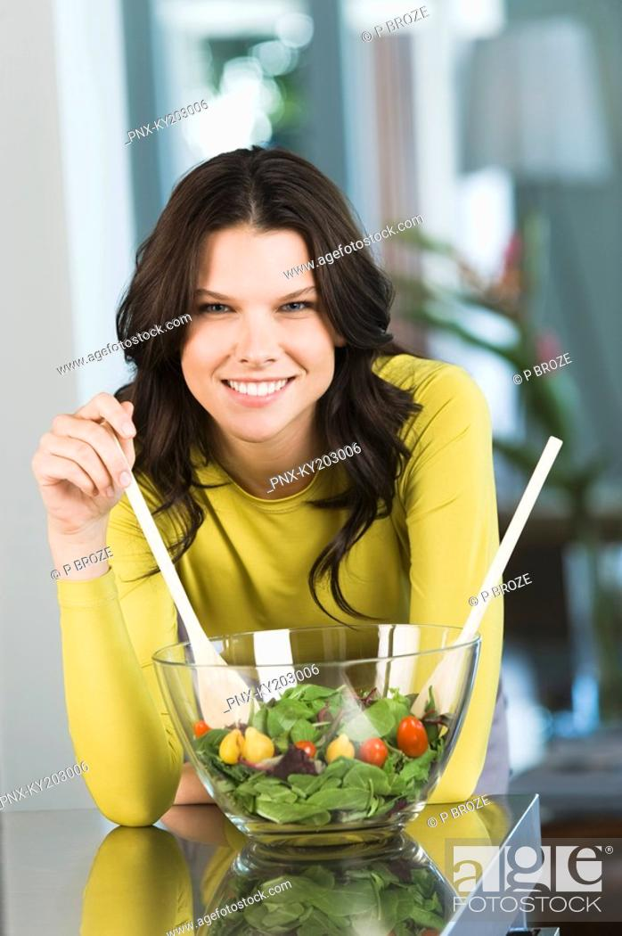 Stock Photo: Portrait of a woman mixing salad.