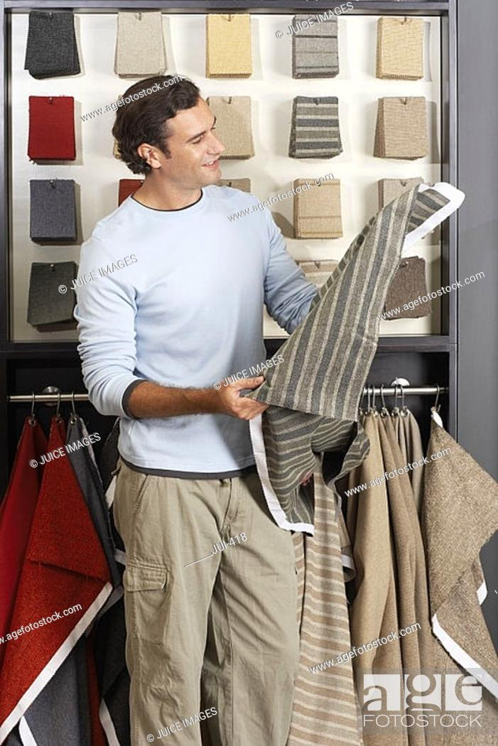 Stock Photo: Man looking at grey fabric swatch in shop, smiling, side view.