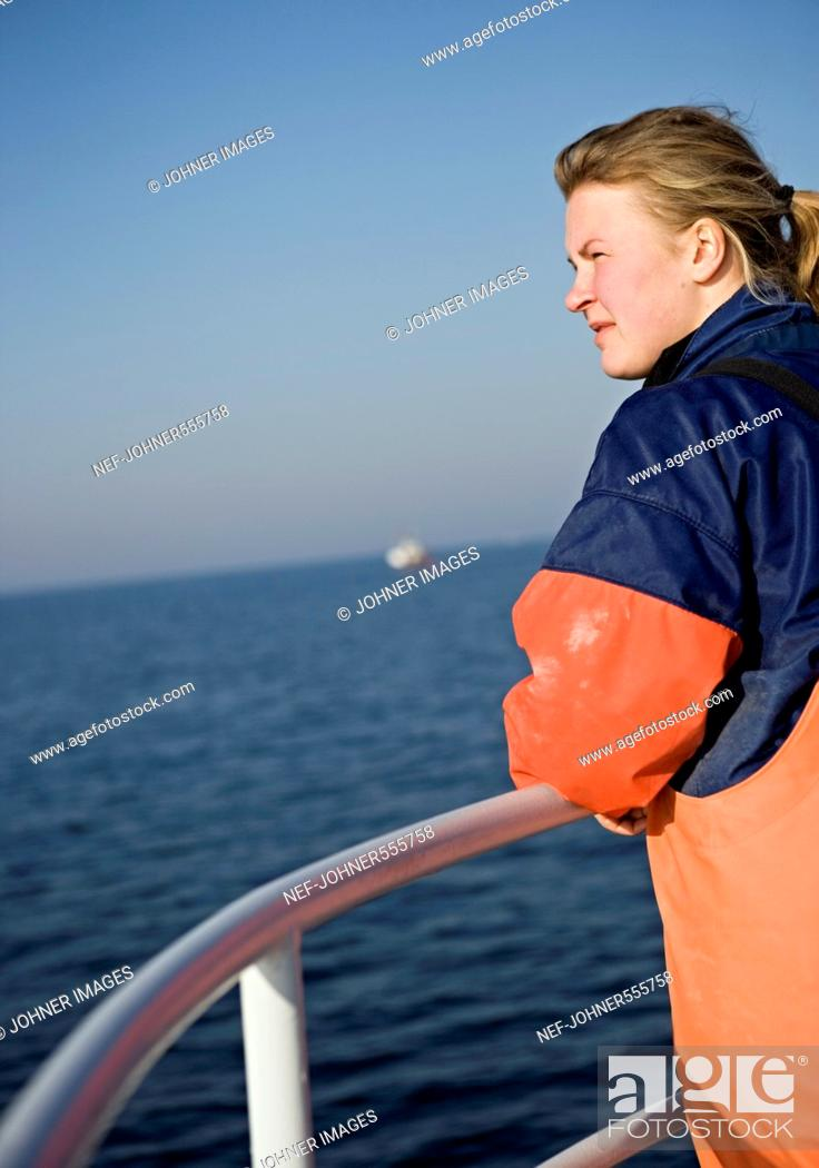 Stock Photo: A fisherman standing by the gunwale of a boat, Koster, Stromstad, Sweden.