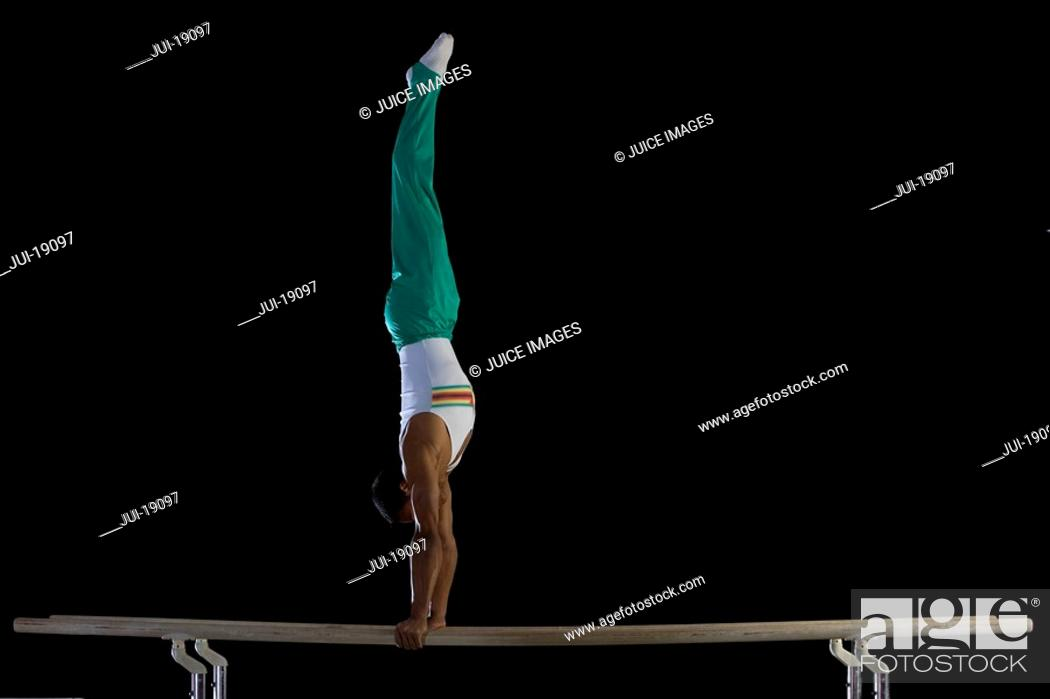 Stock Photo: Male gymnast performing handstand on parallel bars, side view.