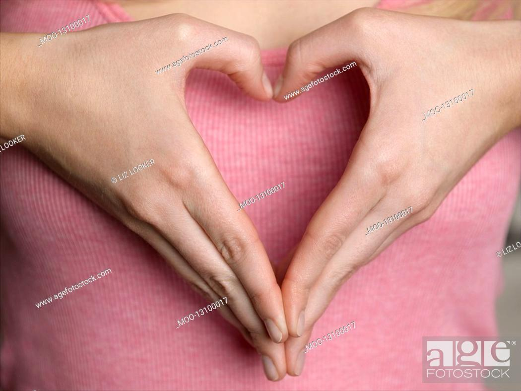 Stock Photo: Woman making heart shape with hands close-up mid section.