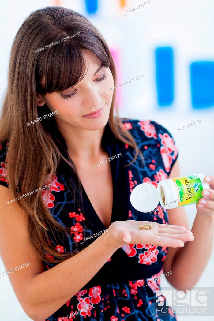 Stock Photo: Woman taking herbal sedative capsules containing extract of the valerian plant Valeriana officinalis.