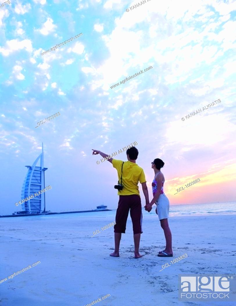 Stock Photo: Western couple on the beach near Burj Al Arab, Dubai, UAE.