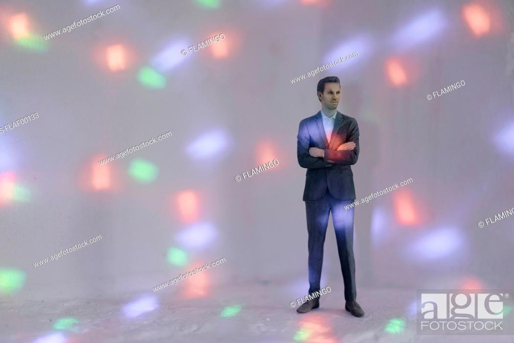 Stock Photo: Miniature businessman figurine surrounded by points of light.