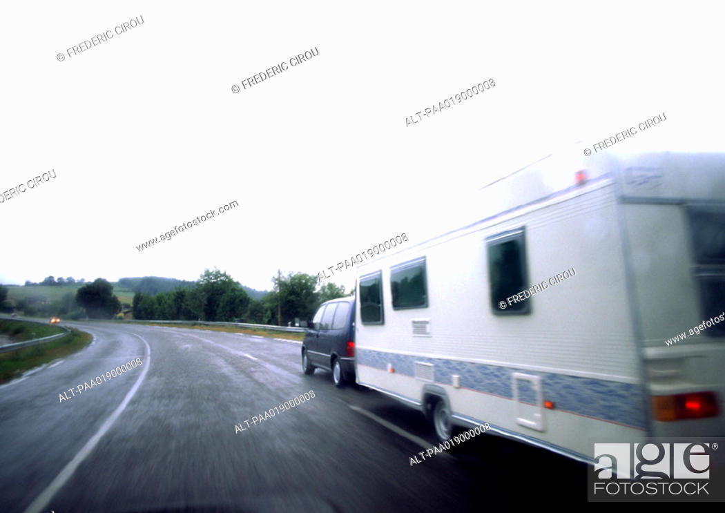 Stock Photo: Car with mobile home driving on road, blurry.