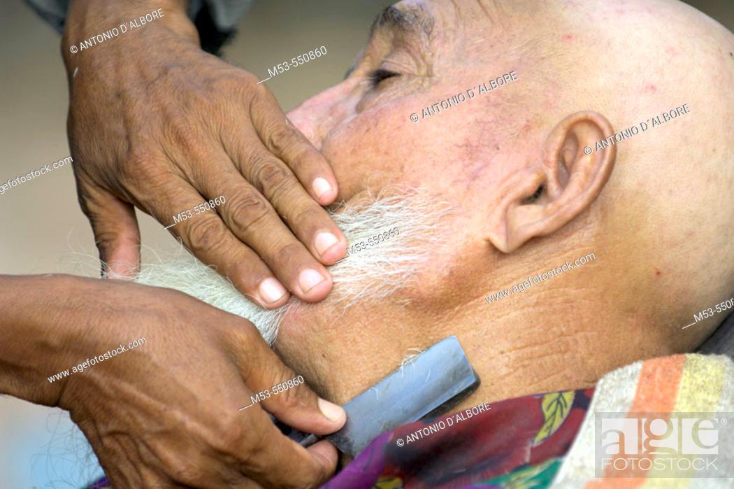 Stock Photo: A barber shave a uigur man. Kashgar city. Xinjiang province. China. Asia.