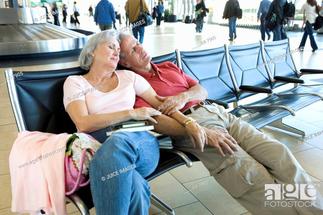 Stock Photo: Senior couple sitting in airport departure lounge, leaning against each other, arm in arm, sleeping.
