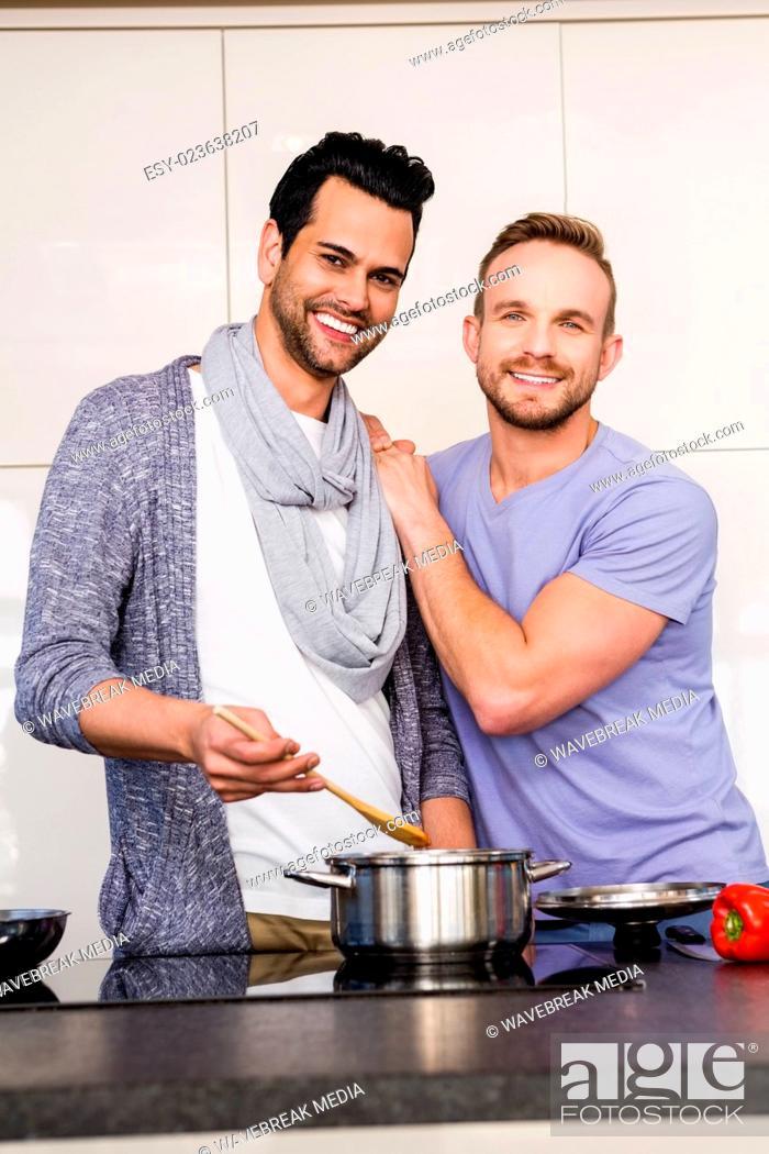 Stock Photo: smiling gay couple preparing food.