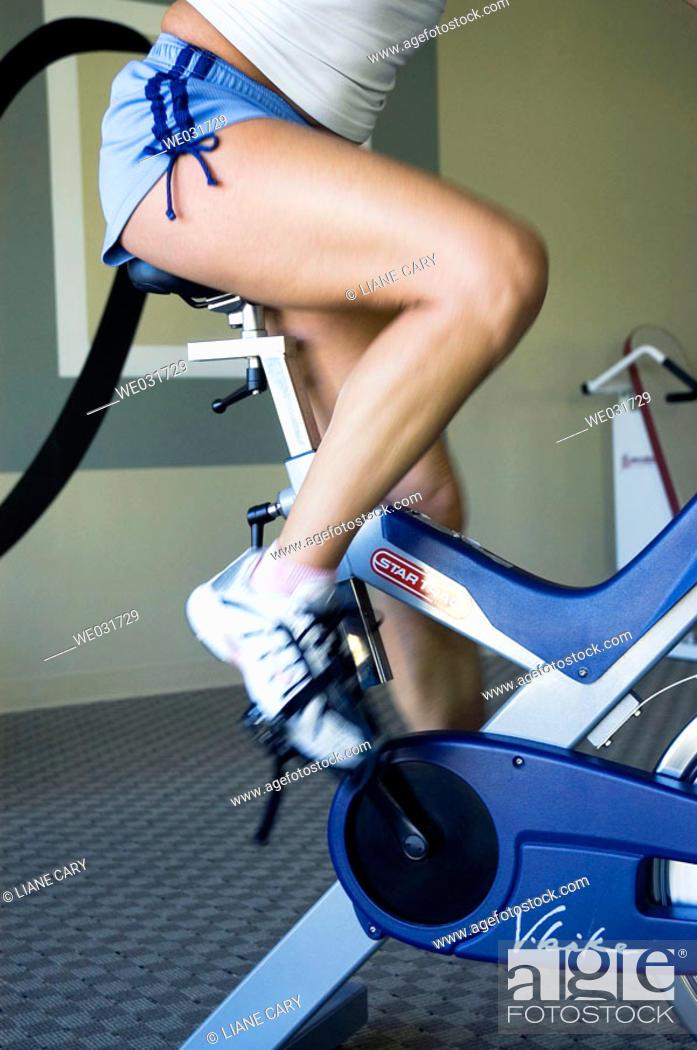 Stock Photo: Woman on exercise bike.