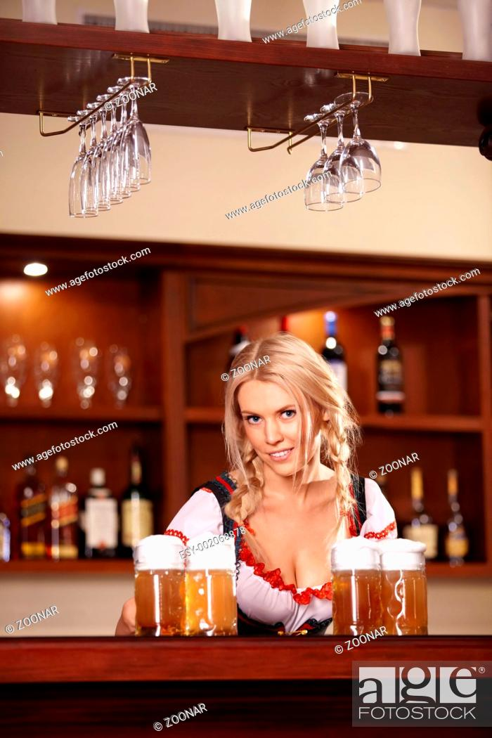 Stock Photo: The nice girl behind the bar with beer.