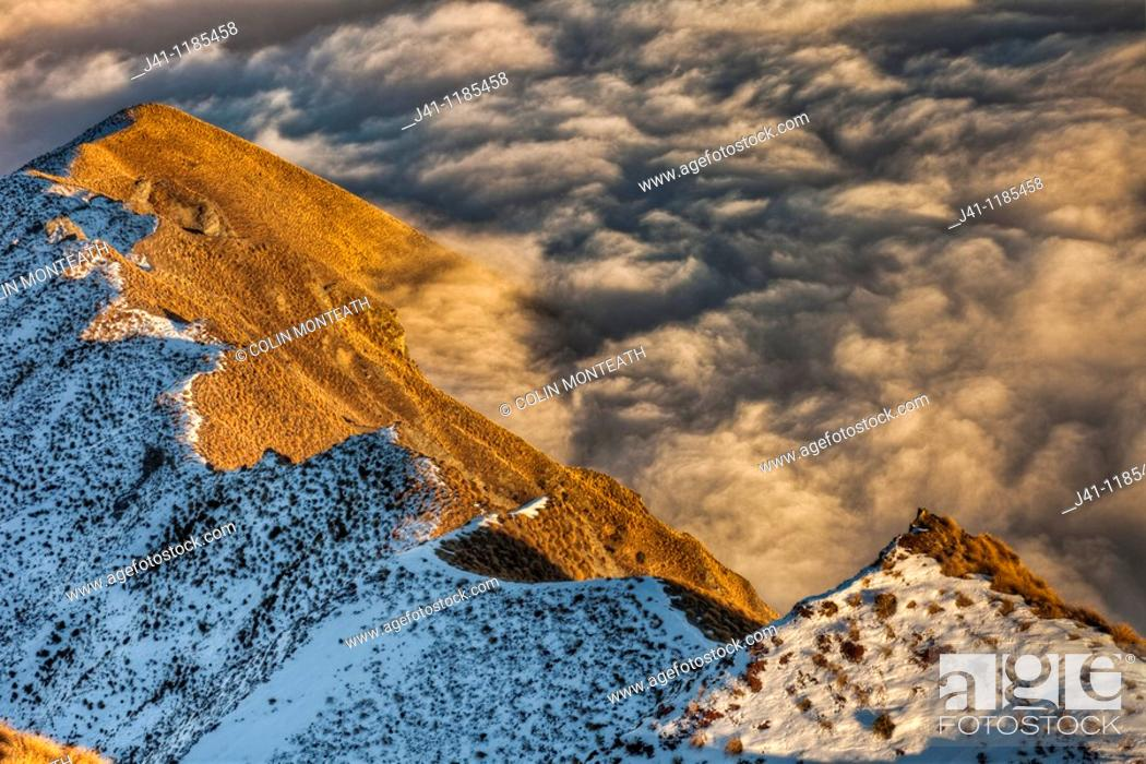 Stock Photo: Tussock covered ridge below Mt Roy partly covered by winter snow, above sea of cloud over Lake Wanaka, Central Otago, Southern Alps, New Zealand.