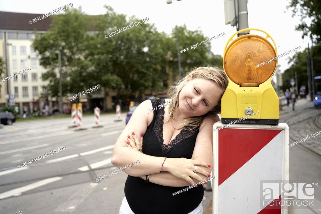 Photo de stock: Woman beside signalling light on the street, Munich, Germany.