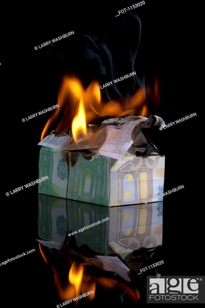 Stock Photo: European Union currency folded into a house and on fire.