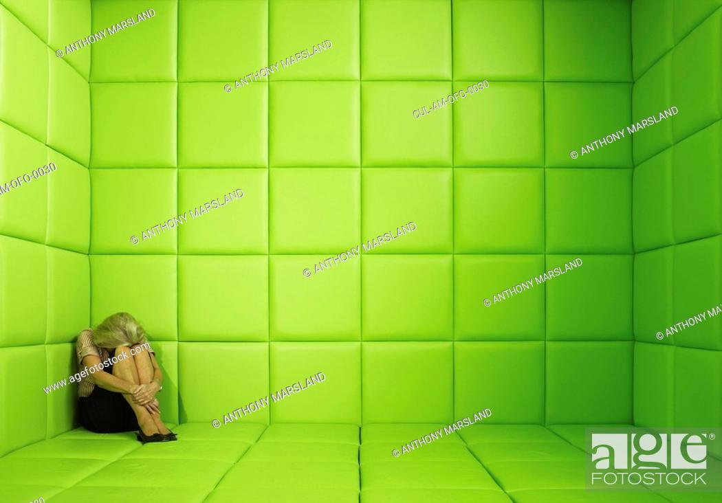 Stock Photo: Woman crouching in corner of green padded cell.