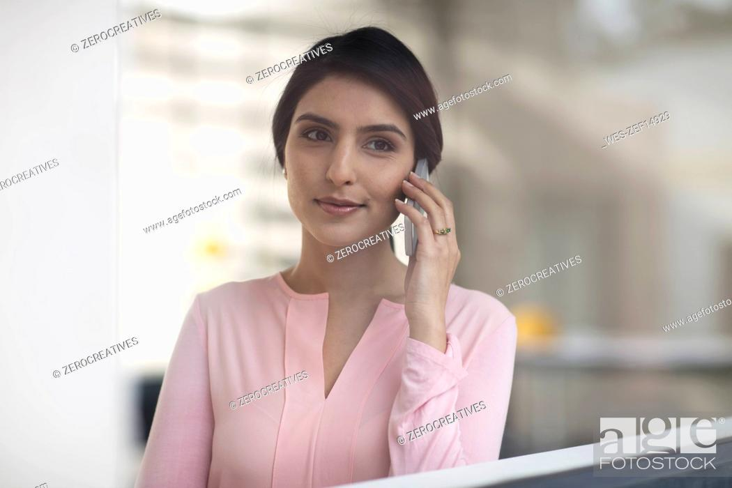 Stock Photo: Portrait of young woman on cell phone in the office.