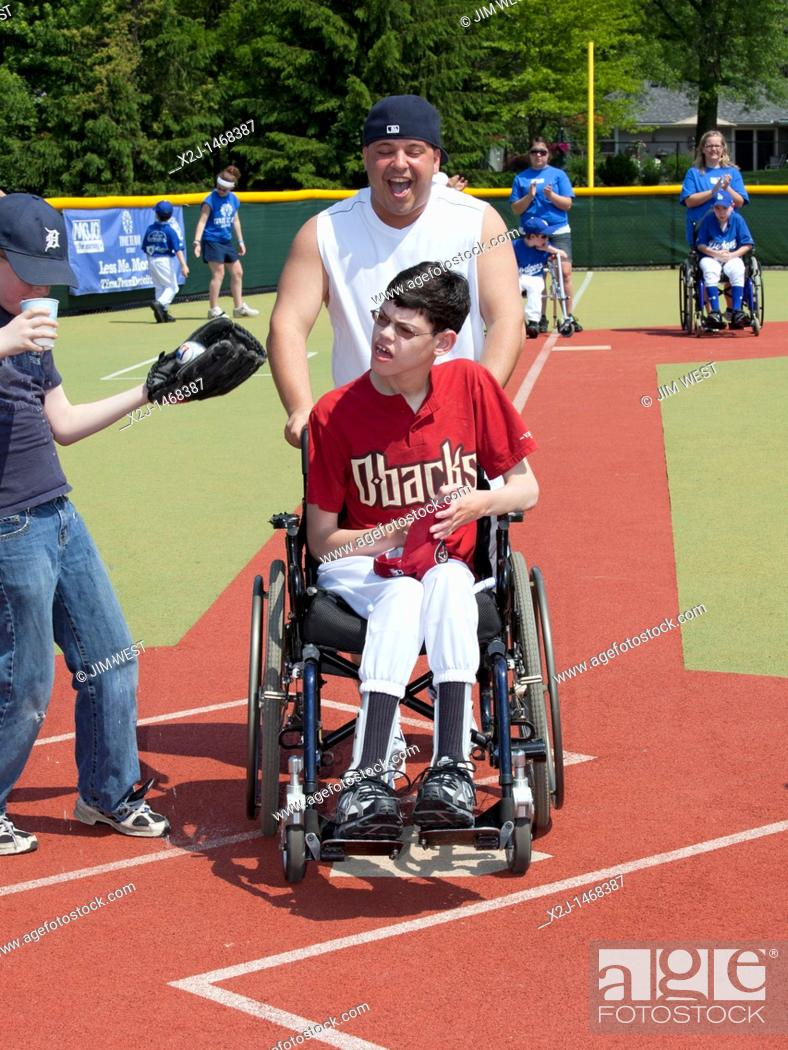 Stock Photo: Southfield, Michigan - Children with disabilities play baseball in the Miracle League  Each child has a buddy who volunteers to help the child, as needed, hit.