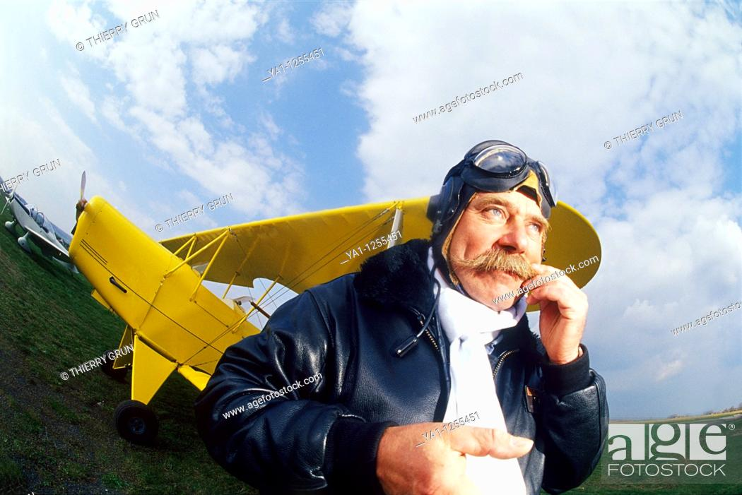 Stock Photo: French pilot scratching his mustaches front of his biplane.