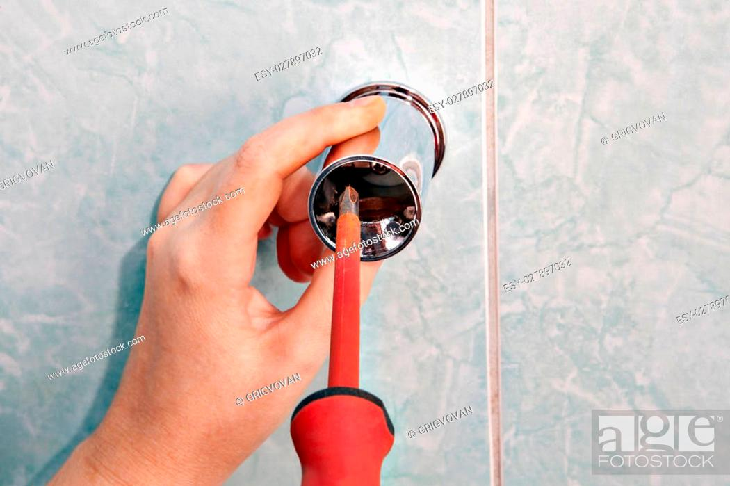 Stock Photo: Residential plumbing repair, remove vertical holder shower slide rail bracket, using screwdriver, close up.