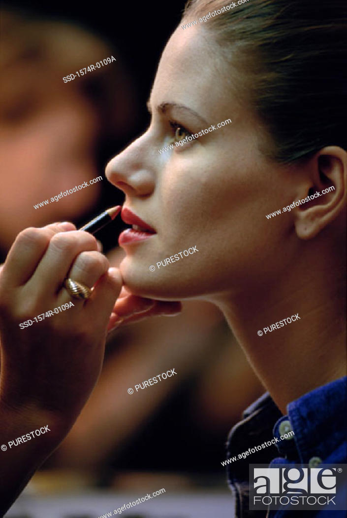 Stock Photo: Side profile of a young woman applying lip liner.