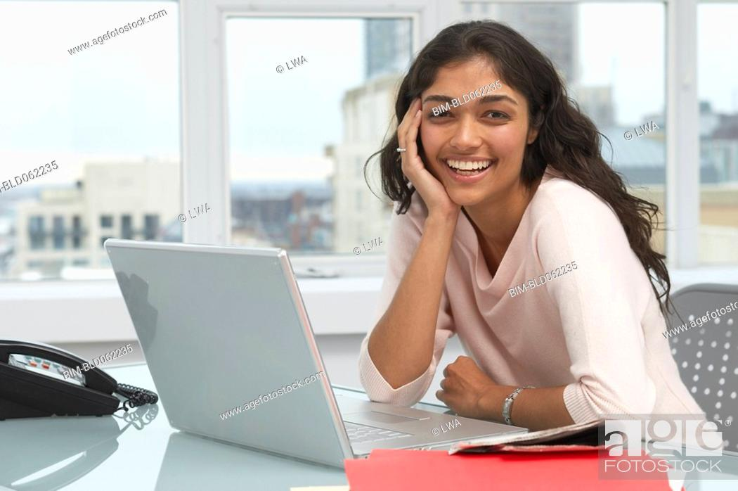 Stock Photo: Trinidadian businesswoman smiling with laptop.