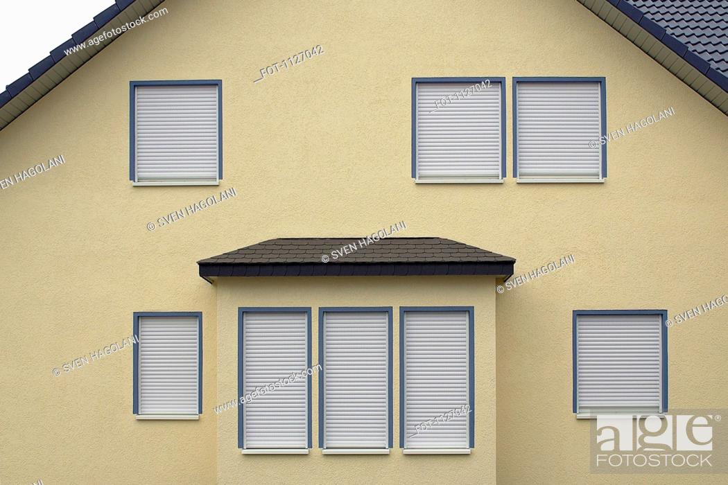 Stock Photo: Side of house with window shutters down.