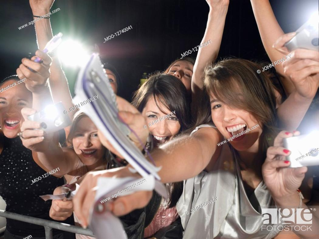 Stock Photo: Fans leaning over barrier.