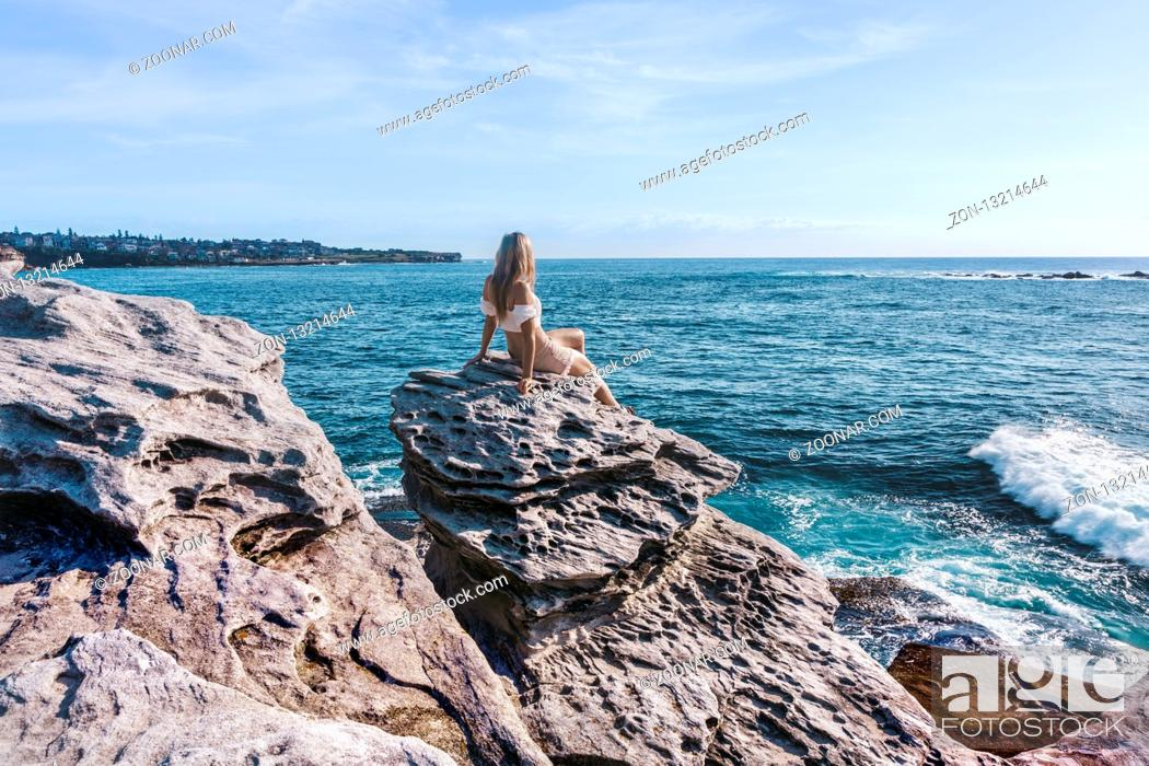 Stock Photo: Female perched on a rock relaxed mode chilling out in teh beautiful morning sunshine with lovely ocean views and sky full of soft wispy clouds.