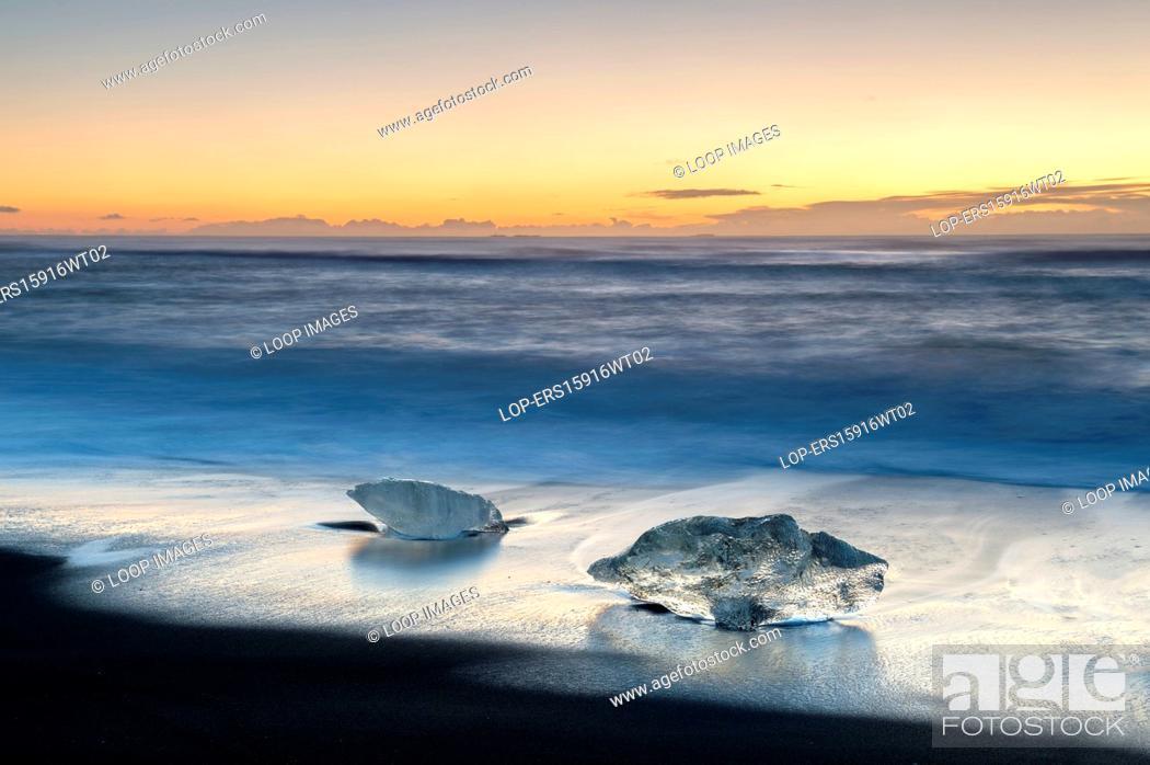 Stock Photo: Icebergs washed up on Jokulsa volcanic beach at sunrise.