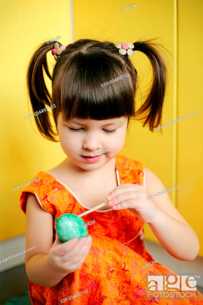 Stock Photo: little Girl paint easter eggs in yellow background. Adorable little girl coloring an Easter egg.