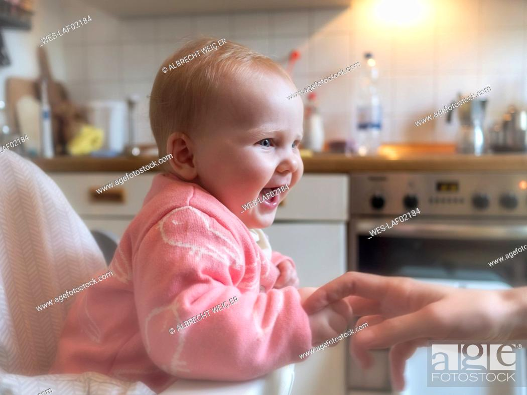Happy Baby Girl In Sitting In High Chair In Kitchen Stock Photo