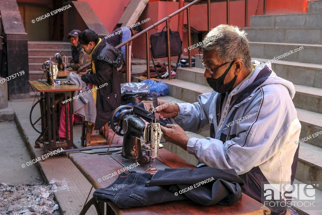 Imagen: Imphal, India - December 2020: Tailors working with a sewing machine on the street on December 30, 2020 in Imphal, Manipur, India.