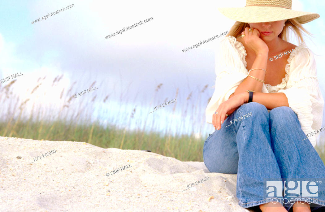 Stock Photo: Young woman on sand dune thinking.