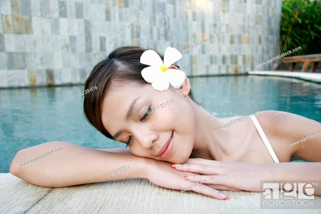 Stock Photo: Portrait of a teenage girl leaning near swimming pool with eyes closed.