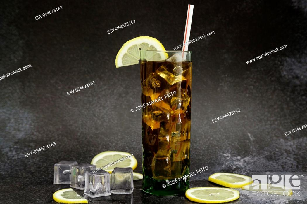 Stock Photo: Iced tea glass with lemon slice and straw, lemon slices and ice cubes on dark background with copy space.