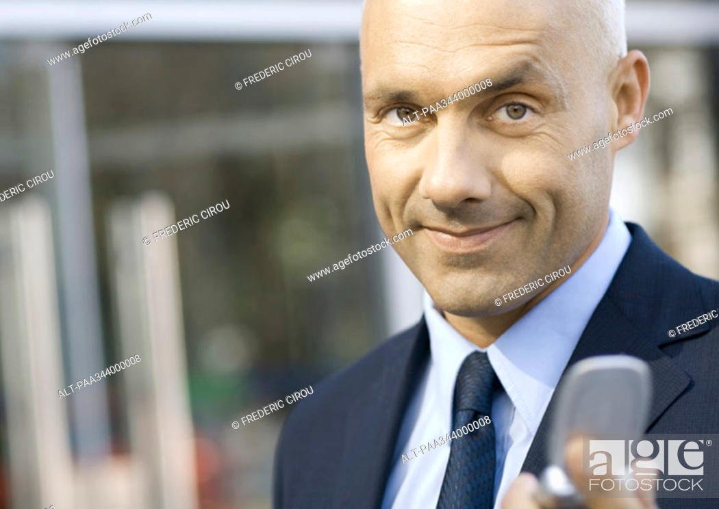 Stock Photo: Businessman holding out cell phone.
