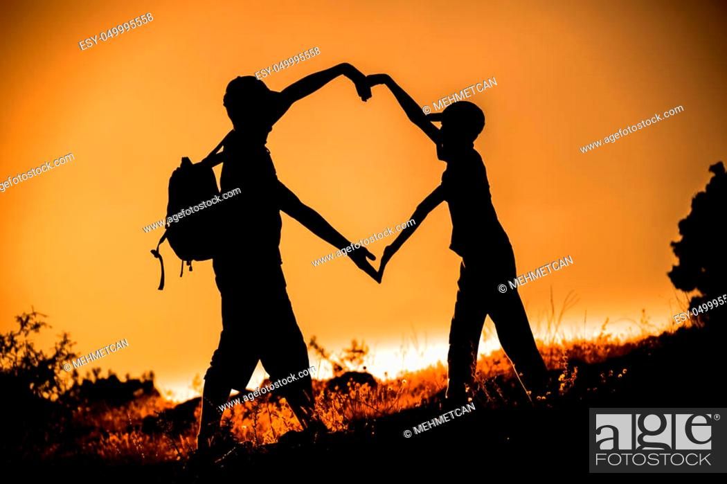 Stock Photo: Silhouetted friend forming a heart symbol at golden hour sunset.