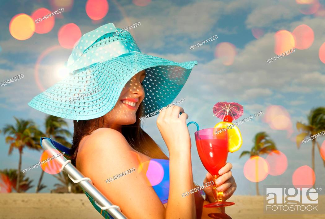 Stock Photo: Young woman sitting on deckchair with cocktail at Miami beach, Florida, USA.