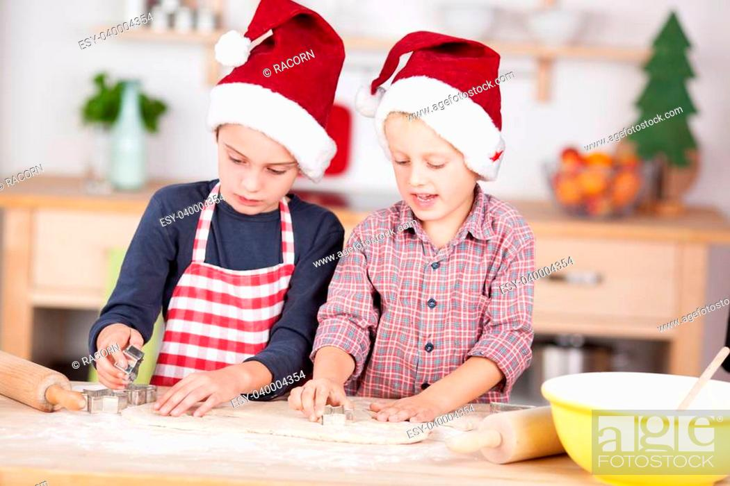 Stock Photo: Two cute Caucasian boys wearing Santa's hats and preparing Christmas cookies with shapes.