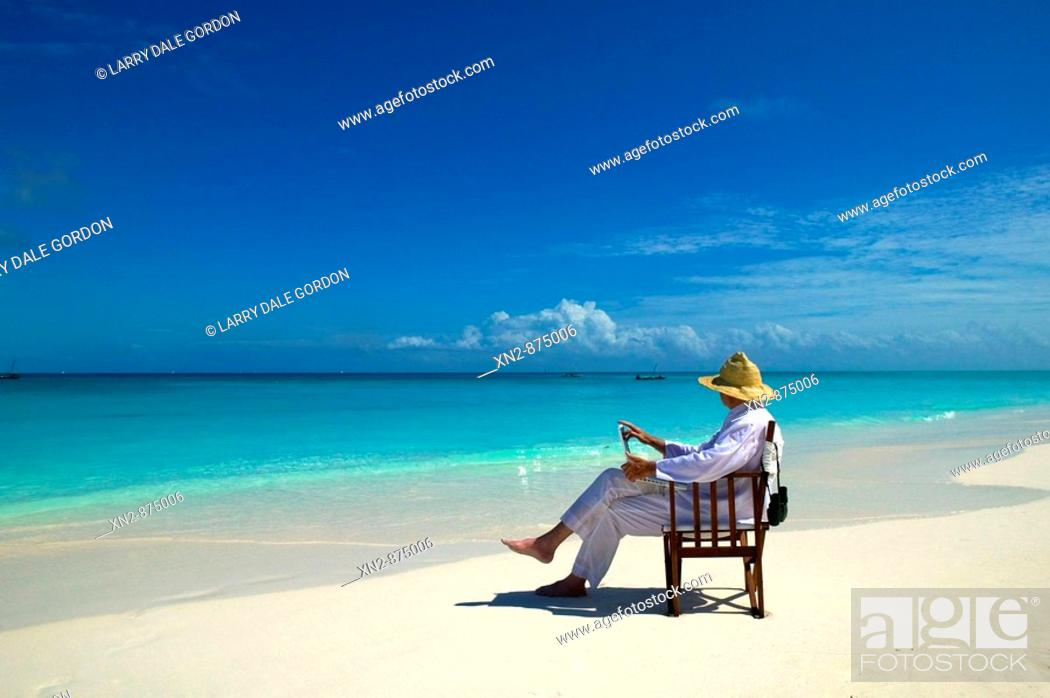 Stock Photo: Tanzania. Mnemba Island. Resort Guest on his laptop on the exquisite beach that fronts the resort.