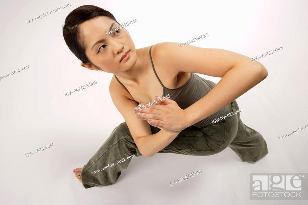 Stock Photo: View of a young woman stretching with folded hands.
