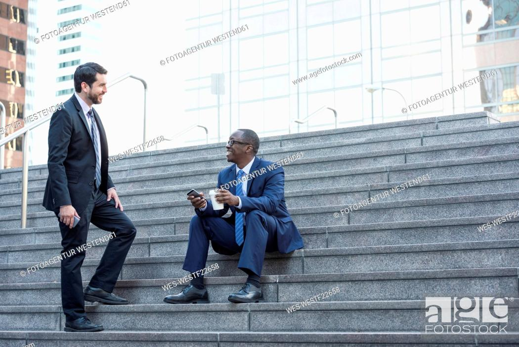 Stock Photo: Two businessmen talking on stairs.
