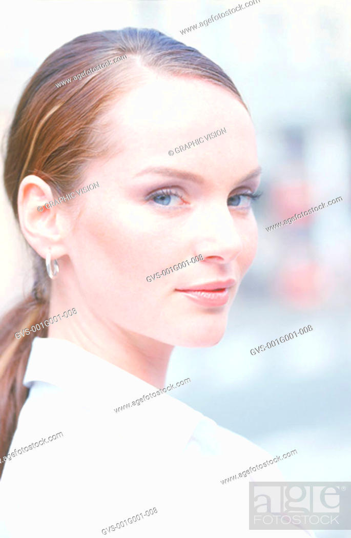 Stock Photo: Portrait of a Young Woman With a Ponytail in a White Shirt.