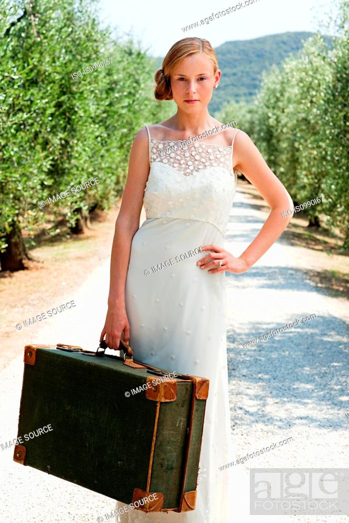 Stock Photo: Bride with suitcase on country road, hand on hip.